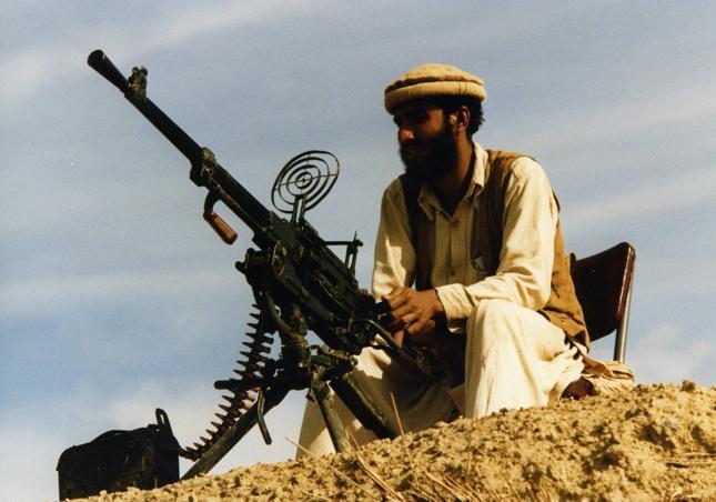 """Plan Regana zakładał obniżkę cen ropy (mniejszy budżet ZSRR) oraz zwiększenie kosztów czerwonego imperium, poprzez """"gwiezdne wojny"""" oraz podtrzymywanie wojny w Afganistanie. Amerykanie wysyłali Mudżahedinom sprzęt oraz doszkalali ich na terytorium Pakistanu. Zdjęcie z 1987 roku przedstawia afgańskiego wojownika, który pełni posterunek przy jednym z takich obozów szkoleniowych"""