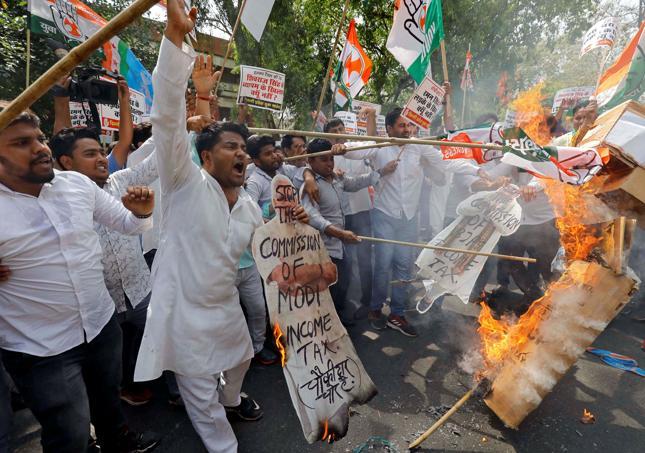 Aktywiście Delhi Pradesh Youth Congress palą podczas protestu wizerunki premiera Narendra Modi oraz szefa rządzącej partii Bharatiya Janata Party - Amita Shaha.