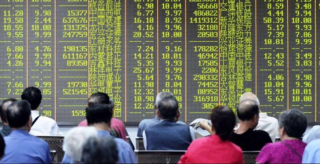 Chińscy inwestorzy obserwują notowania giełdy w Szanghaju. Kolorem zielonym w Chinach oznacza się spadki