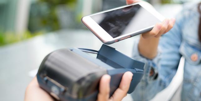 Żeby dokonać płatności smartfonem, wystarczy przystawić go do terminala POS
